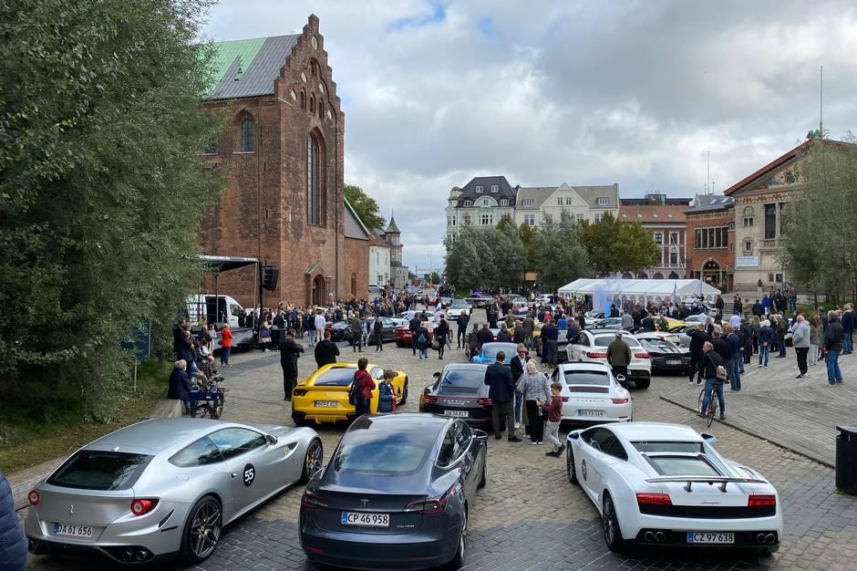 Den ene bil i millionklassen efter den anden holder på række på Bispetorvet her til eftermiddag. Cool Car Race kører i år for 10. gang, og Aarhus er deres næstsidste stop. Sammen med Joey Moe tjener de en (plus-minus) million.